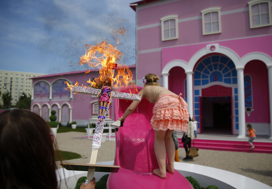 """Activists from women's rights group Femen burn a barbie doll on a cross as they protest outside a """"Barbie Dreamhouse"""" of Mattel's Barbie dolls in Berlin"""